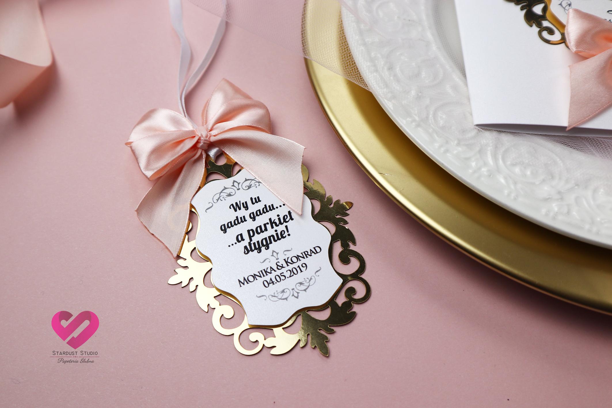 Pastelowe, romantyczne zawieszki ślubne na alkohol w stylu glamour z delikatną różową wstążką i złotym ażurem pasujące do zaproszeń